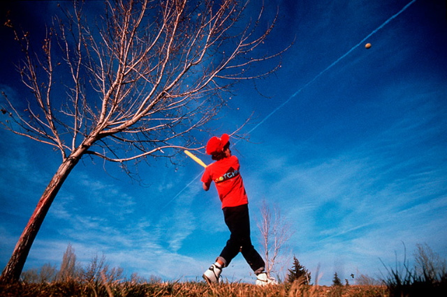 photo of boy in red shirt swinging a baseball bat